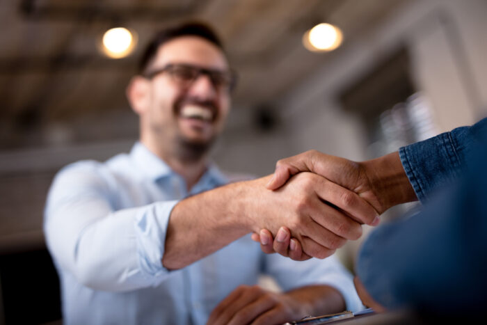 Business person shaking hands with an invoice factoring professional.