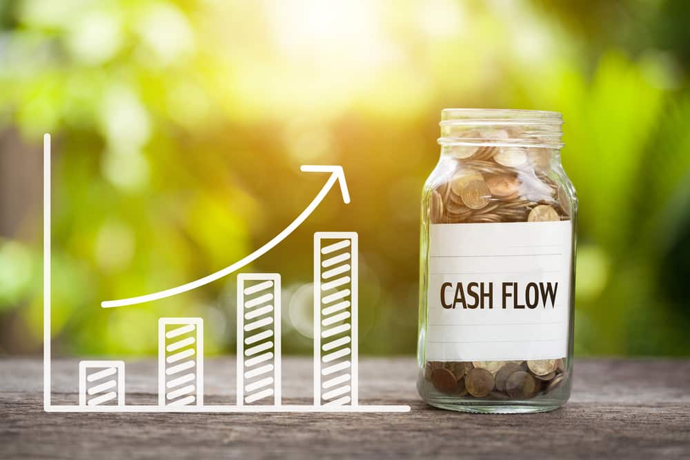 Cash Flow Word With Coin In Glass Jar and graph up